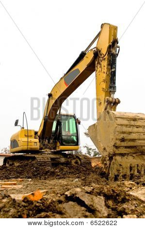 Yellow And Black Dirty Excavator Parked On The Construction Site