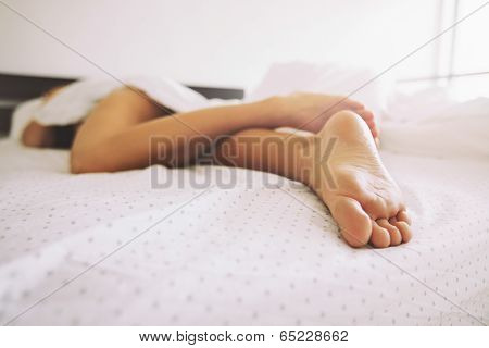 Legs Of A Young Female Sleeping In Bed