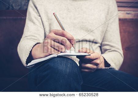 Man On Sofa Taking Notes