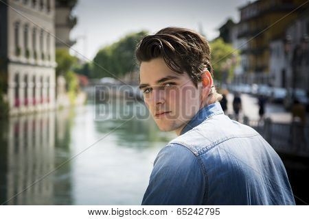 Young Man Wearing Denim Shirt On City Bridge