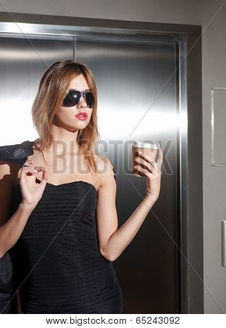 fashion and lifestyle concept - beautiful young woman in sunglasses with take away coffee