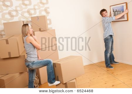 Moving House: Couple Hanging Picture On Wall