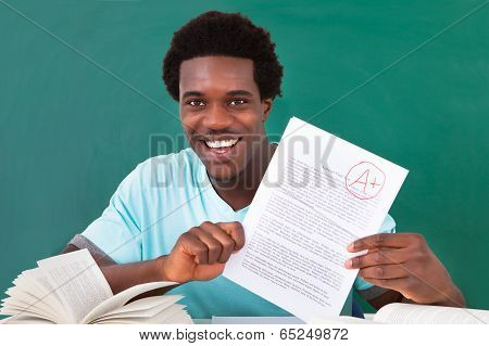 Young Man Showing A Paper With Grade A Plus