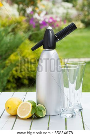 Siphon with soda, citruses and glasses for limonade