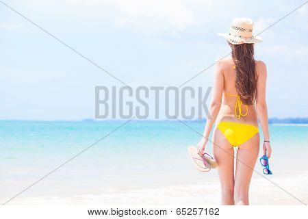 young beautiful woman in yellow bikini and straw sun hat walking on beach. Thailand, Khao Lak