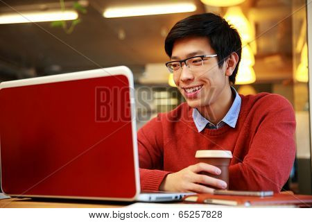 Happy asian man in glasses working on laptop and holding cup of coffee