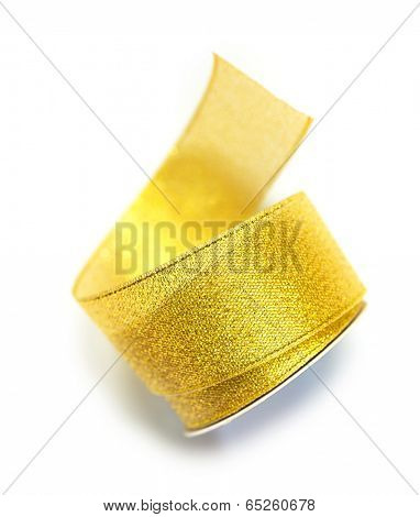 Naturally unwinding coil or reel of gold ribbon. Isolated on white.