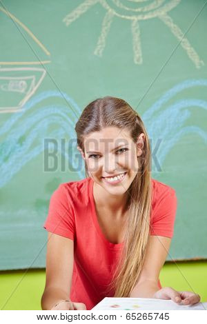 Happy young woman doing education as child care worker in a kindergarten