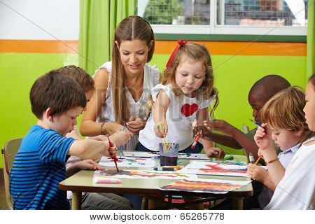 Many children painting together with nursery teacher in a kindergarten