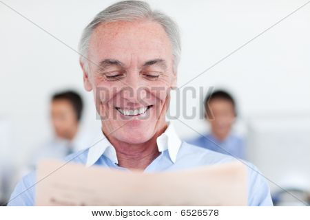 Senior Manager Reading At His Desk