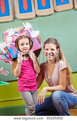 Happy mother with her daughter in DIY costume for carnival in kindergarten