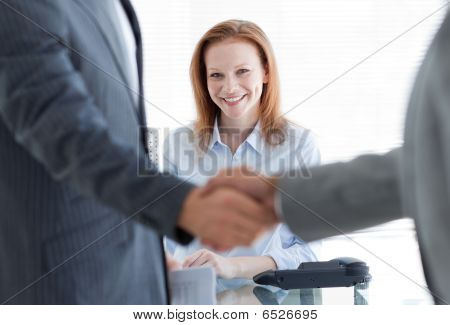Businesswoman Smiling With Businessmen Greeting Each Other In The Foreground