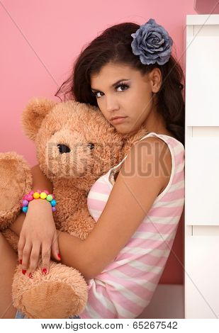 Attractive young girl hugging toy bear, looking at camera.