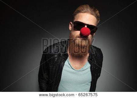 casual young man with a long beard and a clown red nose looking into the camera with his hands at the back. on a dark studio background