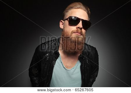 casual young man with a long beard and retro sunglasses looking way from the camera. on a dark studio background