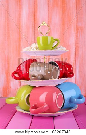 Cups in vase on table on wooden background