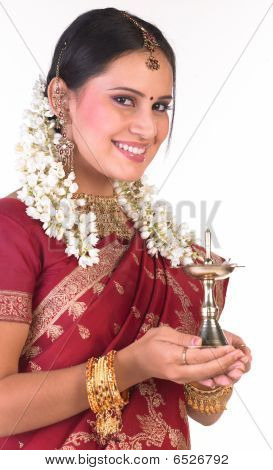 Girl with red silk sari carrying the lamp