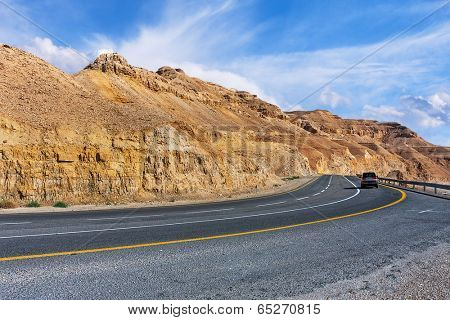 Highway along mountains of Arava desert under beautiful cloudy sky in Israel.