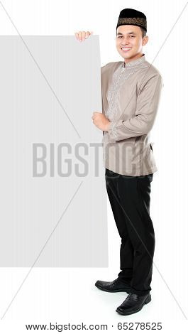 Smiling Asian Muslim Man Presenting Copy Space