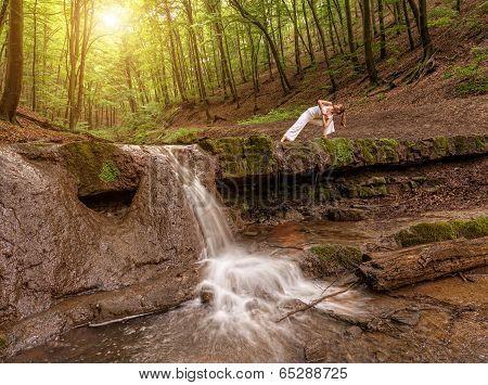 Woman practices yoga in nature the waterfall. parsvakonasana pose