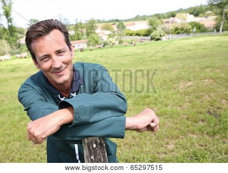 Cheerful farmer standing in country field