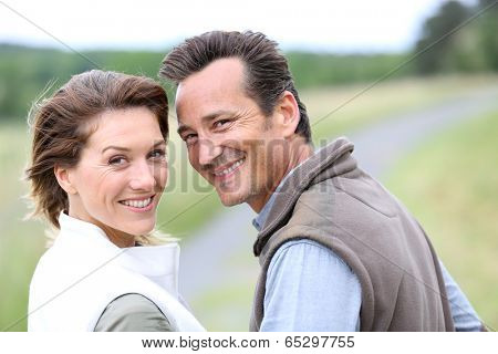 Cheerful 40-year-old couple walking in countryside