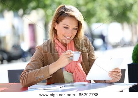 Woman at coffee shop and websurfing with tablet