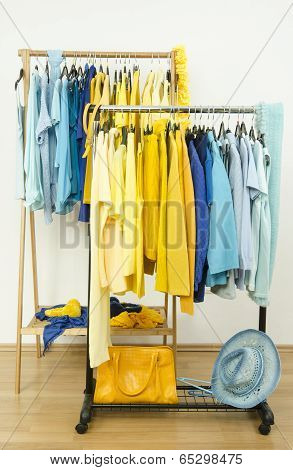 Color coordinated yellow and blue clothes on hangers.