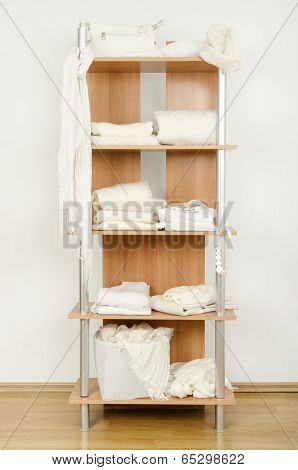 White clothes nicely arranged on a shelf.