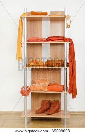 Orange clothes nicely arranged on a shelf.