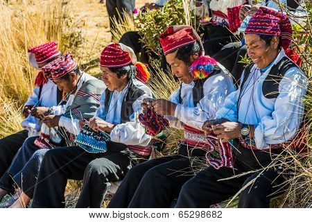 PUNO, PERU - JULY 25, 2013: men weaving in the peruvian Andes at Taquile Island