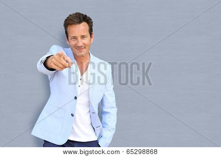 Mature man on grey background pointing at camera