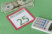stock photo of overspending  - Calendar page with currency and a calcular for a tight budget this Holiday season - JPG