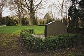 stock photo of empty tomb  - An empty cemetery with a single gravestone - JPG