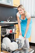stock photo of dishwasher  - Happy Woman Putting Utensils In Dishwasher For Cleaning - JPG