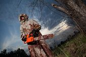 foto of man chainsaw  - Maniac with the chainsaw dressed in a dirty bloody raincoat. Sunset forest on the background