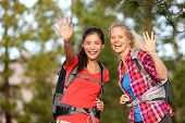 picture of say goodbye  - Hiking women waving hello with hands smiling at camera happy during hike trek outdoors in forest - JPG
