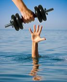 picture of dumbbell  - Giving dumbbell to sinking man instead of help - JPG