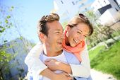 pic of piggyback ride  - Man giving piggyback ride to woman in town - JPG