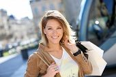 stock photo of tram  - Cheerful woman with shopping bags in town - JPG