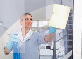 stock photo of maids  - Young Happy Maid Holding Bottle And Cloth - JPG