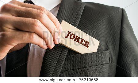 Businessman Putting Wooden Piece With Joker Text In Pocket