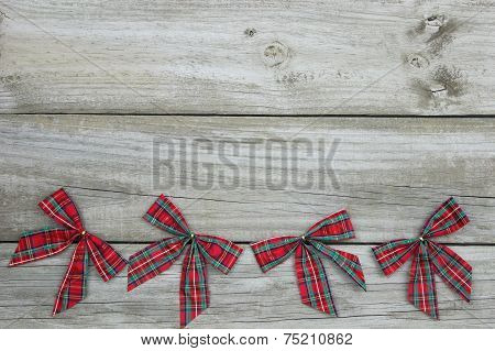 Plaid Christmas bows border with weathered wooden background