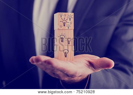 Businessman Holding Cubes With Drawn Light Bulbs