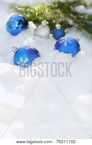 Close Up Of Decorative Christmas Balls On The Snow And Branch Of Christmas Tree Outdoor