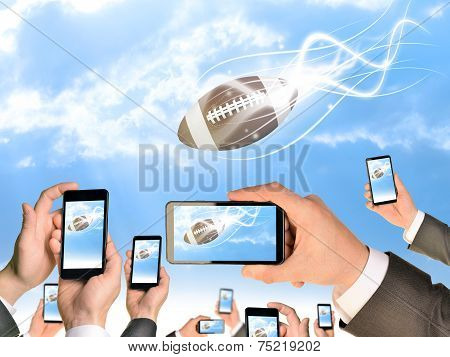 Hands holding smart phones and shoot video as falling American football
