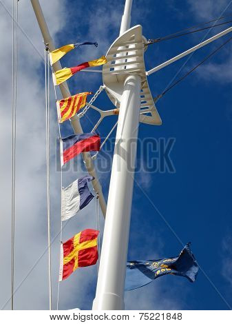 Nautical Flags Hanging From A Ship's Mast With Wispy Clouds