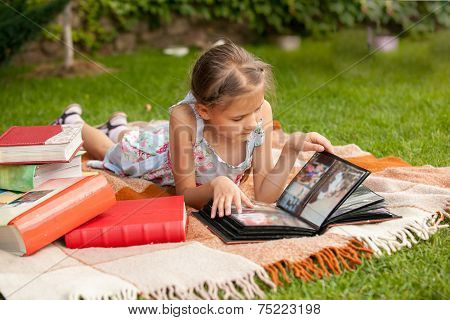 Girl At Park Looking At Family Photo Album