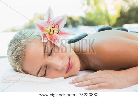 Side view of a beautiful young woman receiving stone massage at health farm