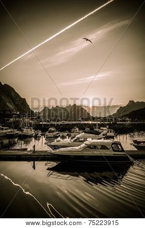 Yachts and boats near moorage at sunset in Reine village, Norway